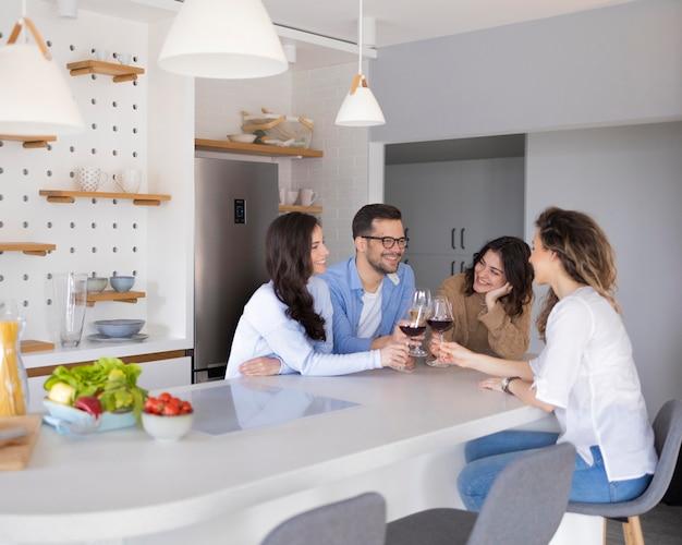 キッチンでワインを飲む友人のグループ