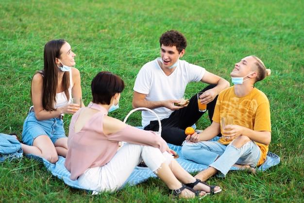 ピクニックで楽しんで、食べたり飲んだりする友人のグループ
