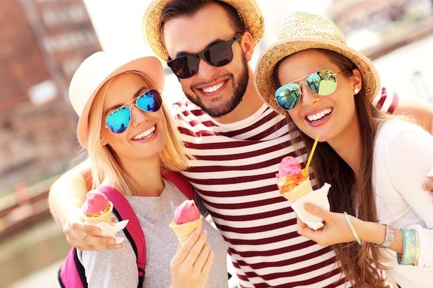 グダニスクの大きな車輪の前でアイスクリームを食べる友人のグループ