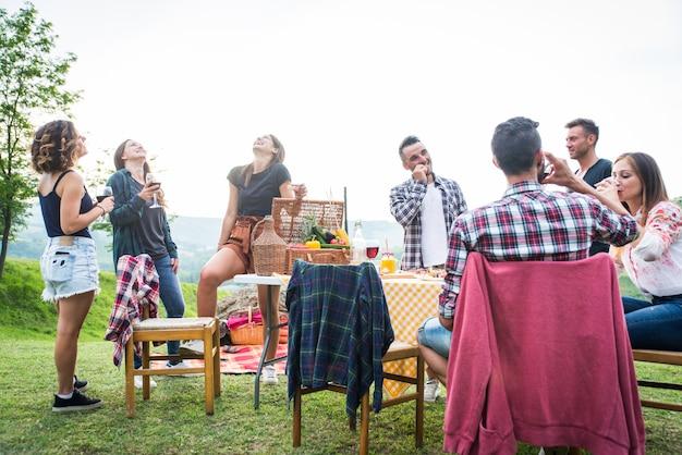 自然の中で食べている友人のグループ