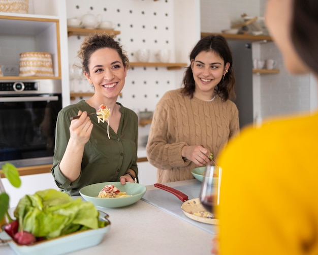 キッチンで一緒にパスタを食べる友達のグループ