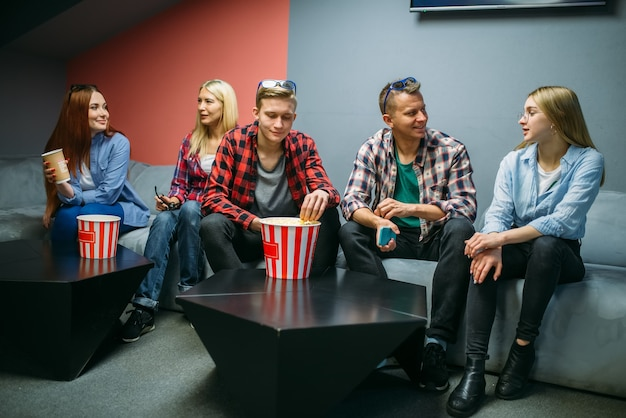 Группа друзей ест попкорн и ждет начала сеанса в кинозале. мужская и женская молодежь, сидя на диване в кинотеатре