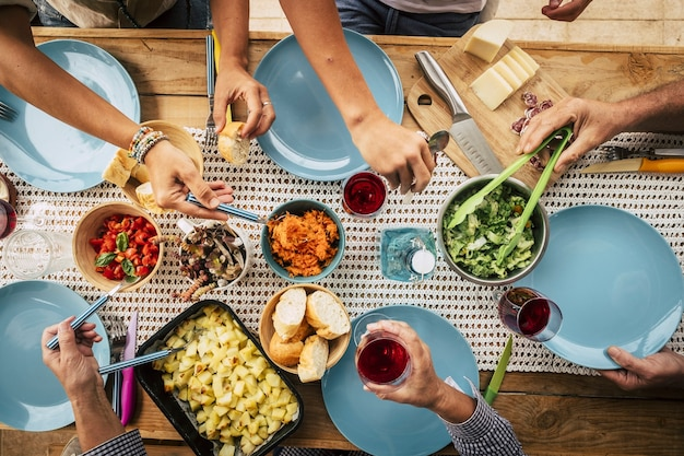 ダイニングテーブルでグラスワインと一緒に食事をしている友人のグループ。皿の上のボウルから食べ物を取る手。懇親会で様々な食べ物や飲み物を楽しむ人々のグループ