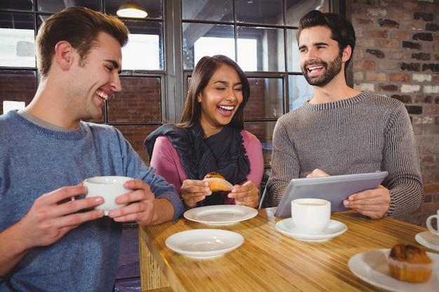 タブレットでデザートを楽しむ友人のグループ