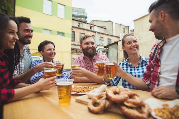 Группа друзей, наслаждаясь напитком в баре на открытом воздухе