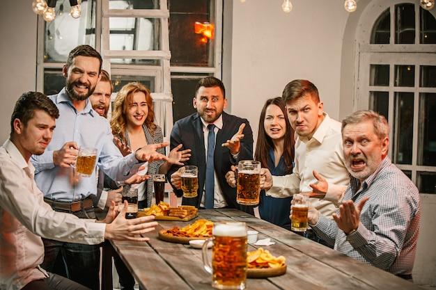 나무 테이블에 맥주와 함께 저녁 음료를 즐기는 친구의 그룹