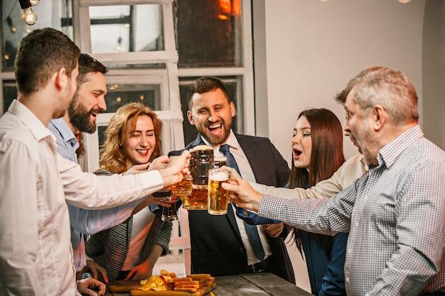 ビールとイブニングドリンクを楽しんでいる友人のグループ