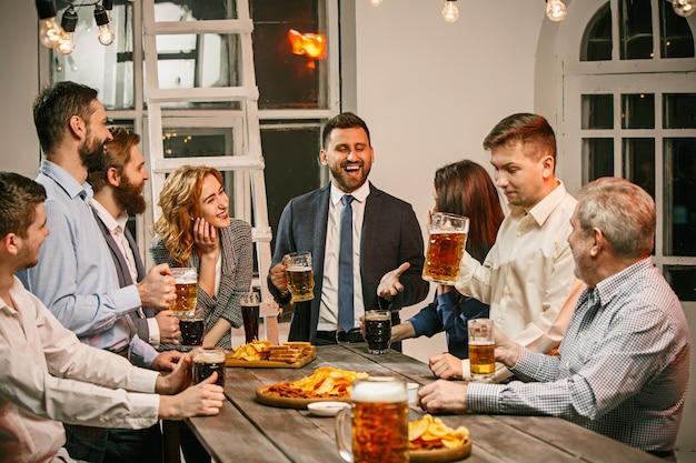 Группа друзей, наслаждающихся вечерними напитками с пивом