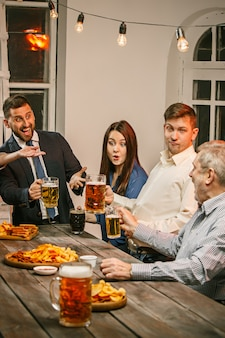 Группа друзей, наслаждаясь вечерними напитками с пивом