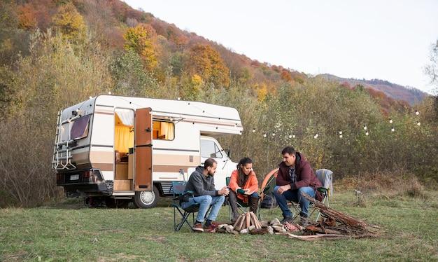 산에서 함께 시간을 즐기는 친구들. 친구 캠핑과 백그라운드에서 복고풍 캠퍼 밴.