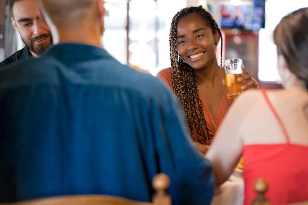바에서 맥주 한 잔을 마시며 함께 즐기는 친구들. 친구 개념입니다.