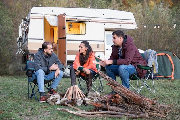 街の激越から逃げ出し、レトロなキャンピングカーで山でキャンプする友人のグループ。