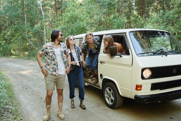 キャンプのために森に行くバンから降りる友人のグループ