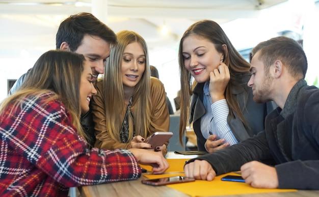 携帯電話を使ってバーに座ってお互いにぶらぶらしている友人のグループ