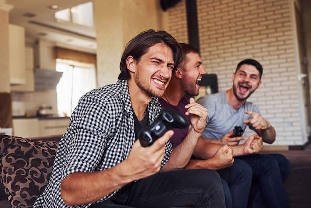 Группа друзей весело проводит время, играя в консольную игру в помещении в гостиной.