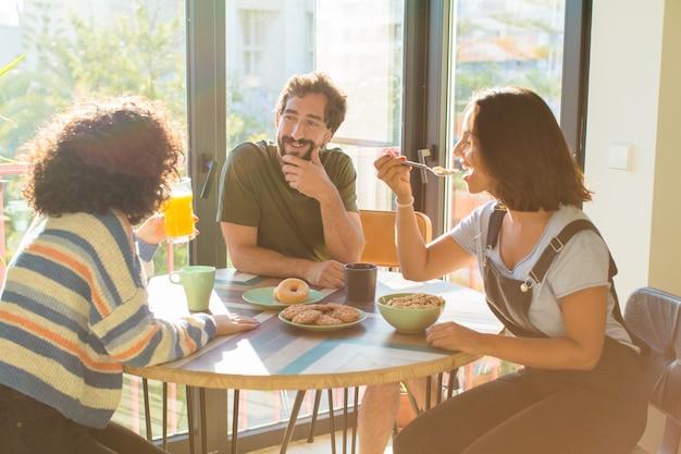 新しい家で一緒に朝食をとっている友人のグループ