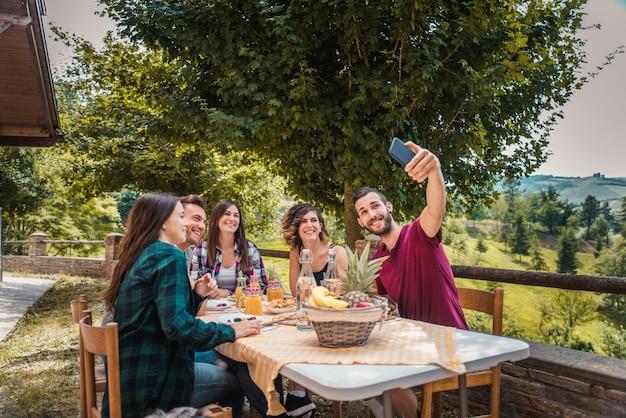 Группа друзей, имеющих завтрак в фермерском доме