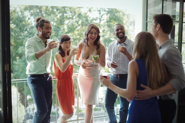 互いに対話しながらカクテルを飲む友人のグループ