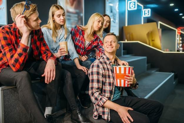 Группа друзей развлекается в кинозале перед началом сеанса. мужская и женская молодежь ждет в кинотеатре