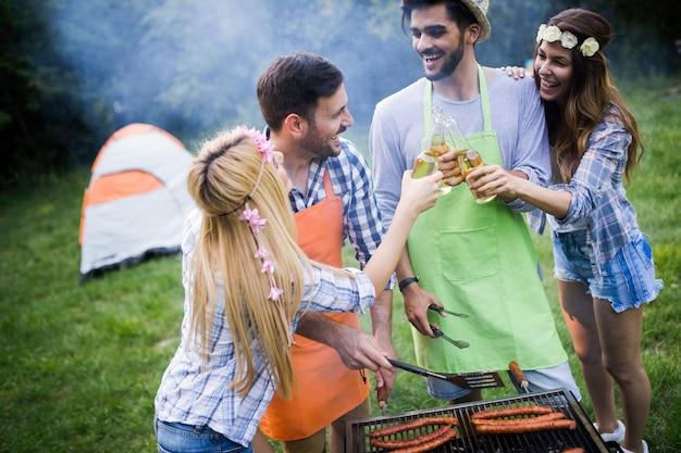 바베큐를 하며 자연에서 즐거운 시간을 보내는 친구들
