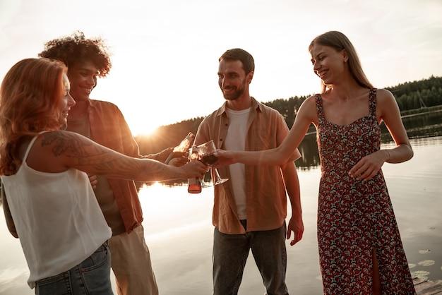 호수나 강 근처에서 피크닉을 즐기고, 와인, 맥주, 사과주를 마시며 건배를 하며 술잔을 기울이며 즐거운 시간을 보내는 친구들. 시골에서 일몰 동안 야외에서 파티를 하는 웃고 있는 젊은이들.