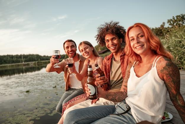호수 근처에서 피크닉을 즐기고 나무 부두에 앉아 와인, 맥주, 사이다를 먹고 마시는 친구들. 시골에서 일몰 동안 야외에서 파티를 즐기는 웃고 있는 젊은이들