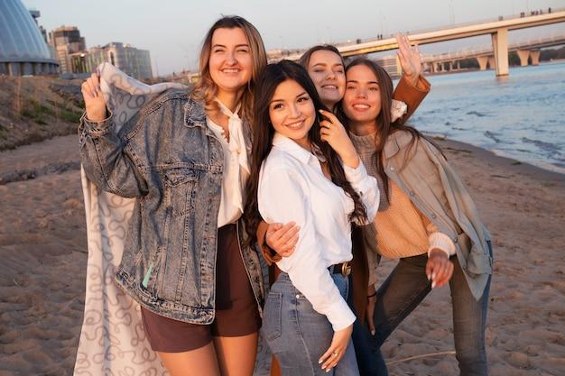 Группа друзей, весело проводящих время на пляже, встречая друзей молодых женщин