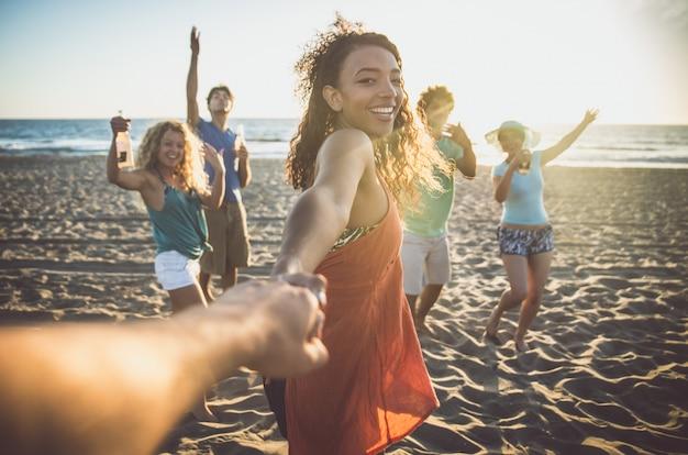 Группа друзей, развлекаясь на берегу моря