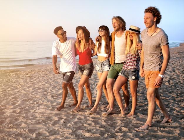 太陽が降り注ぐビーチで楽しんでいる友人のグループ