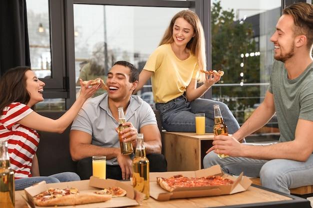 카페에서 맛있는 피자와 함께 즐거운 파티를 하는 친구들