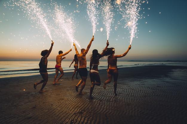 Группа друзей весело бегать по пляжу с бенгальскими огнями