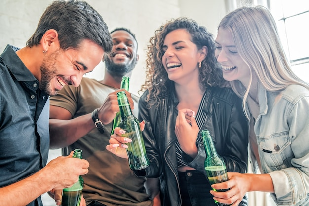 自宅のパーティーでボトルからビールを飲みながら楽しんでいる友人のグループ。