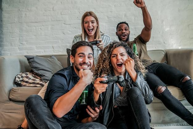 家で一緒にビデオゲームをしながら楽しんでいる友人のグループ。友達のコンセプト。 Premium写真