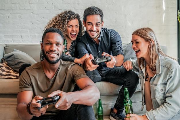 家で一緒にビデオゲームをプレイしながら楽しんでいる友人のグループ。友達のコンセプト。
