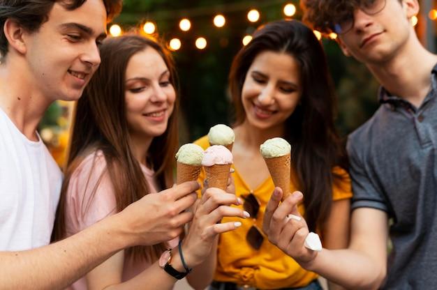 屋外で一緒にアイスクリームを持っている友人のグループ