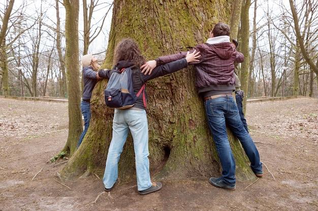 Группа друзей, обнимая гигантский ствол дерева и держась за руки во время пешеходной экскурсии
