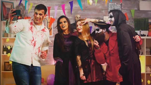 Группа друзей в костюмах, делающих селфи на вечеринке в честь хэллоуина.