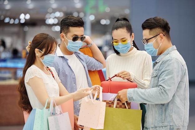 Группа друзей в медицинских масках показывает друг другу, что они купили на рождество