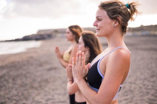 바다 앞 해변에서 명상 활동을하는 친구 그룹. 자연을 사랑하고 건강을 지키는 아름다운 사람들을위한 행복과 힐티 라이프 스타일. 행복하고 인생을 즐기는 것이