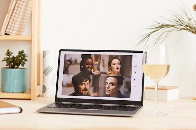 Группа друзей за монитором ноутбука разговаривает друг с другом во время онлайн-трансляции, сидя дома