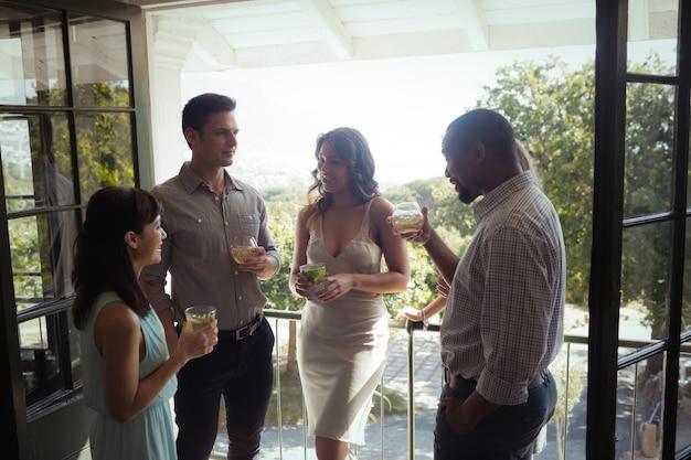 Группа друзей, общающихся друг с другом за коктейлем