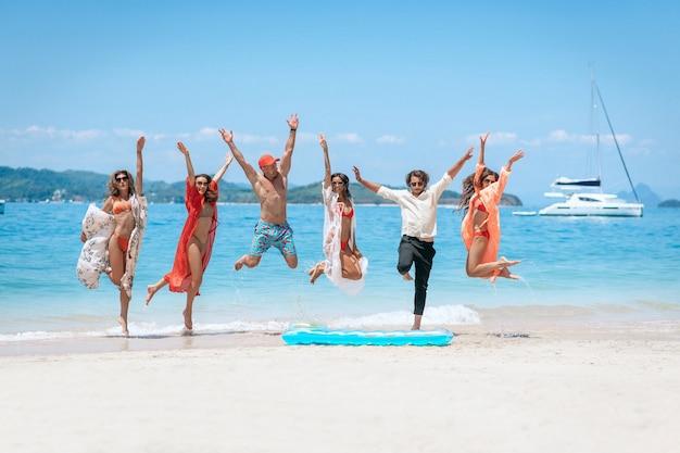 ビーチでジャンプする友人のグループ