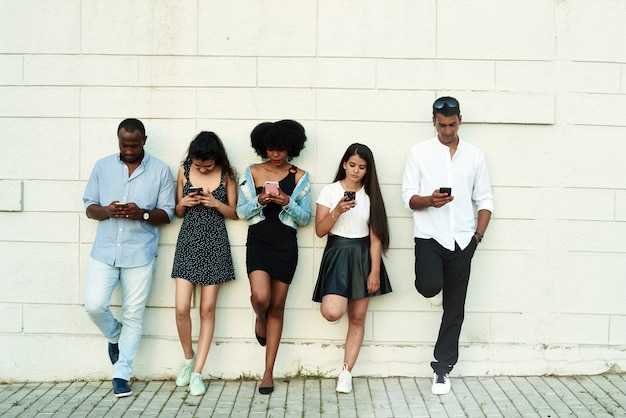 彼らがスマートフォンを見ている何かを笑っている友人のグループ。
