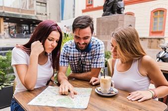 Group of friends looking at map in restaurant