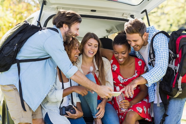 Группа друзей, глядя на мобильный телефон