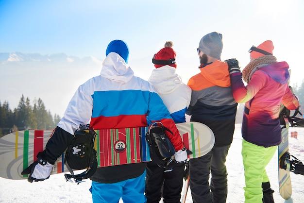 山の景色を見ている友人のグループ