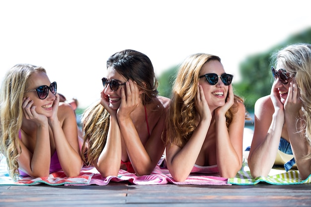 Группа друзей, лежащих возле бассейна