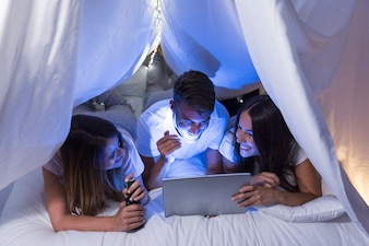 Group of friends lying on bed making fun while watching on laptop