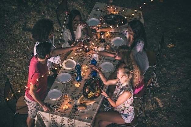 夕食時に裏庭でバーベキューを作る友人のグループ