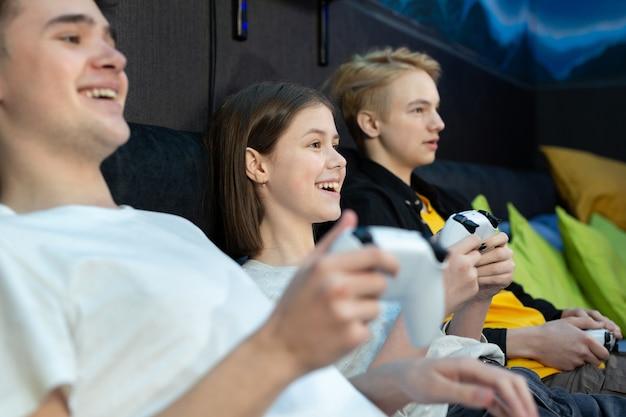 ゲーム クラブのコンソールでビデオ ゲームをしている 10 代の若者、男の子と女の子の友人のグループ。